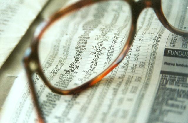 brýle položené na výkazech z akciového trhu